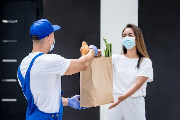 Il giovane corriere che indossa una maschera protettiva e guanti consegna merci a una giovane donna durante la quarantena