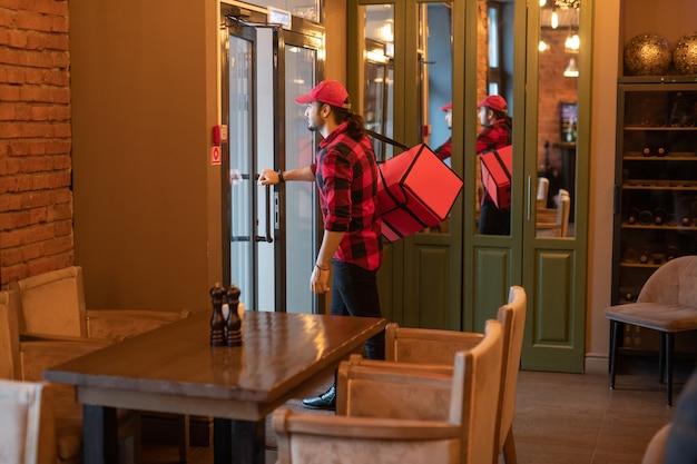Giovane stilista con grande borsa rossa sulla spalla andando ad aprire la porta del bar mentre si allontana per consegnare gli ordini ai clienti