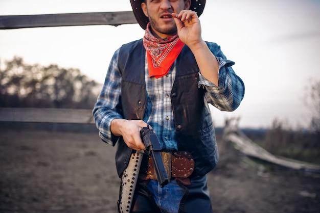 Il giovane cowboy con la pistola posa contro il recinto del cavallo