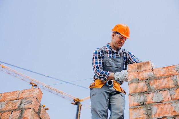 Giovane artigiano che costruisce una casa