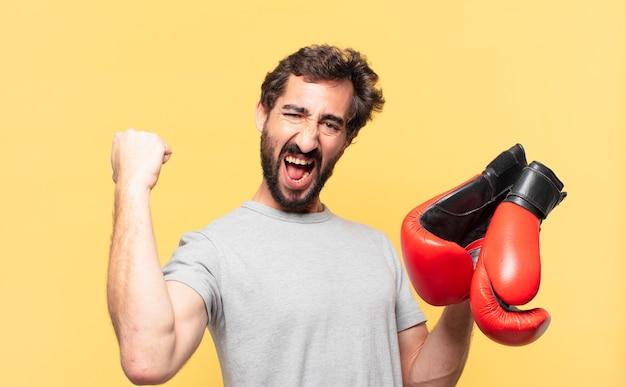 Giovane atleta barbuto pazzo che celebra con successo una vittoria e tiene in mano un guantone da box