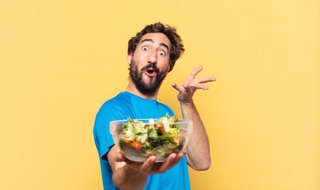 Giovane atleta barbuto pazzo ha sorpreso l'espressione e il concetto di dieta