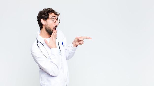Giovane barbuto pazzo uomo medico sulla parete dello spazio di copia