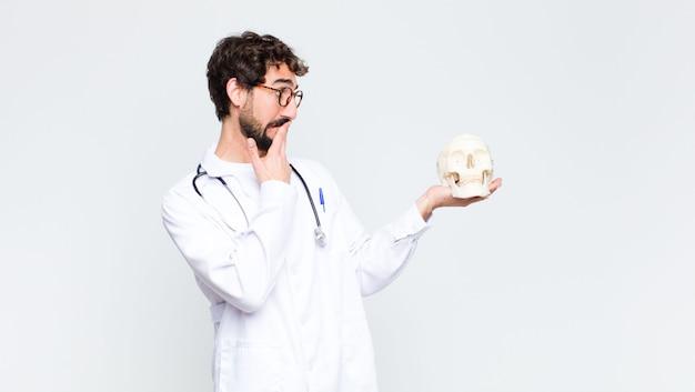 Giovane barbuto pazzo uomo medico che tiene un teschio umano