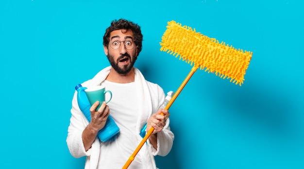 Giovane governante barbuta pazza con prodotti per la pulizia