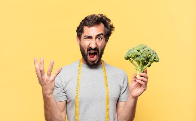 Giovane uomo barbuto pazzo che fa un'espressione arrabbiata a dieta e tiene un cavolo