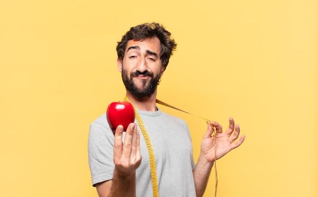 Giovane uomo barbuto pazzo che è a dieta espressione felice e tiene in mano una mela