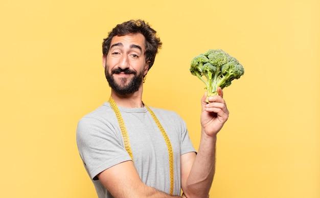 Giovane uomo barbuto pazzo che è a dieta espressione felice e tiene un cavolo