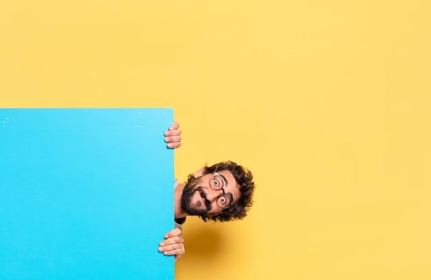 Giovane uomo barbuto pazzo che esprime un'emozione con uno spazio di copia