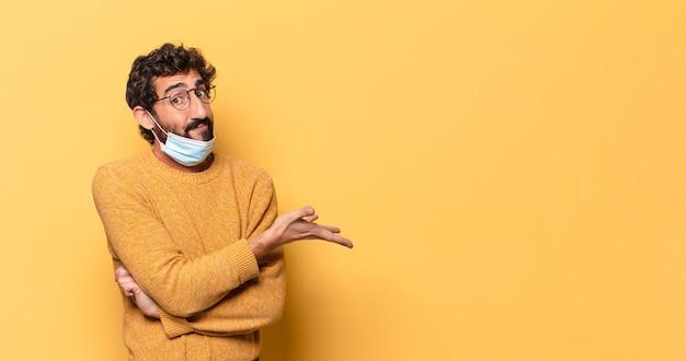 Giovane uomo barbuto pazzo che esprime con uno spazio di copia
