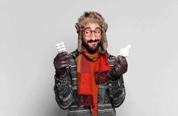 Giovane uomo barbuto pazzo. espressione felice e sorpresa e indossa abiti invernali. concetto di malattia