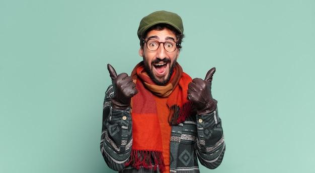 Giovane uomo barbuto pazzo. espressione felice e sorpresa e indossa abiti invernali