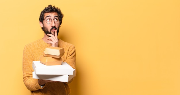 Giovane uomo barbuto pazzo avendo take away fast food con uno spazio di copia