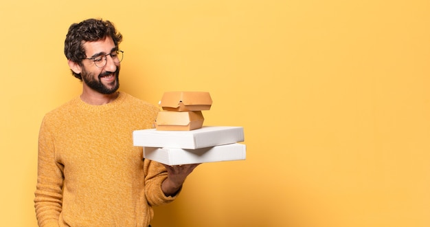Giovane uomo barbuto pazzo che porta via il fast food con uno spazio di copia