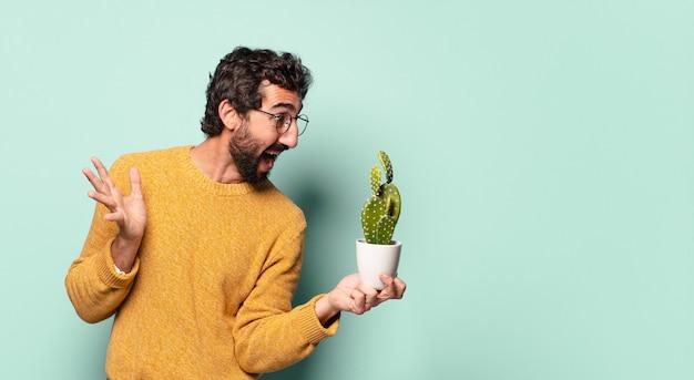 Giovane uomo barbuto pazzo che tiene una pianta della casa del cactus