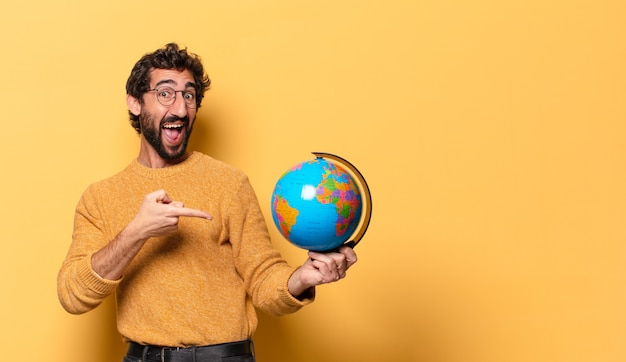 Giovane uomo barbuto pazzo che tiene una mappa del globo del mondo