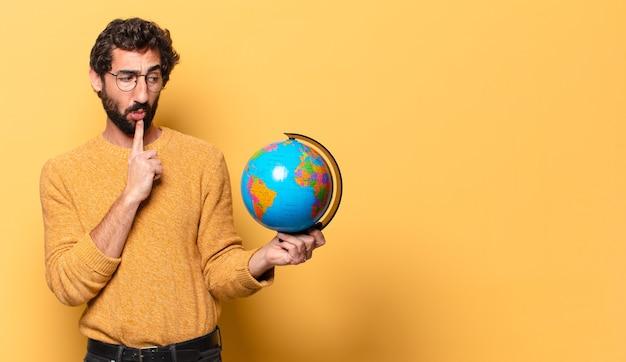 Giovane uomo barbuto pazzo che tiene una mappa del globo del mondo.