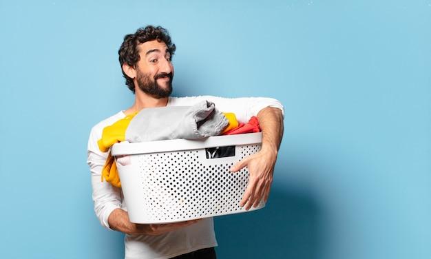 Giovane uomo barbuto pazzo che pulisce i vestiti di lavaggio