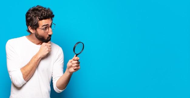 Giovane uomo barbuto pazzo cercando e cercando di trovare con una lente d'ingrandimento