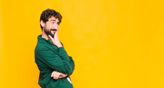 Giovane uomo barbuto pazzo sullo spazio della copia parete arancione.