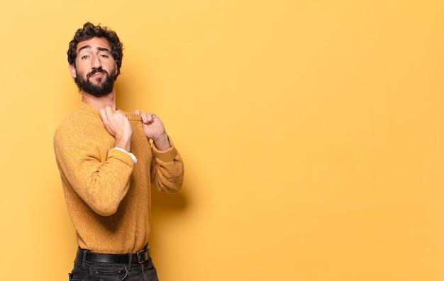 Giovane uomo barbuto pazzo che tira il suo maglione