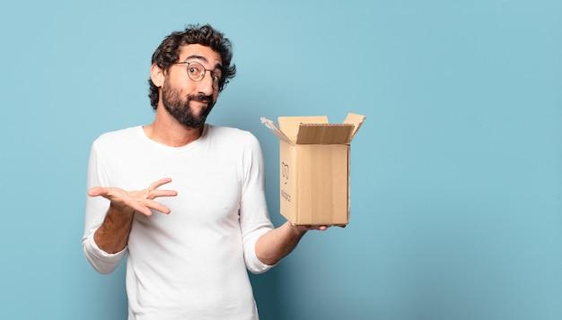Giovane uomo barbuto pazzo che recibing un pacchetto di cartone