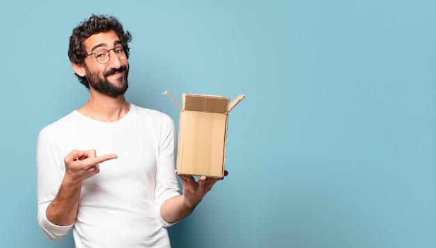 Giovane pazzo barbuto che recita un pacco di cartone