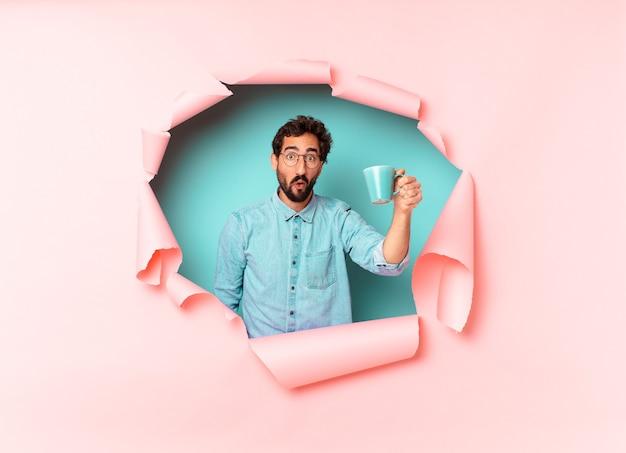Giovane uomo barbuto pazzo. espressione scioccata o sorpresa. concetto di caffè