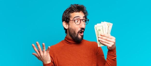 Giovane uomo barbuto pazzo. espressione scioccata o sorpresa. concetto di banconote in dollari