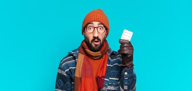 Giovane uomo barbuto pazzo. espressione scioccata o sorpresa e indossa abiti invernali. concetto di malattia