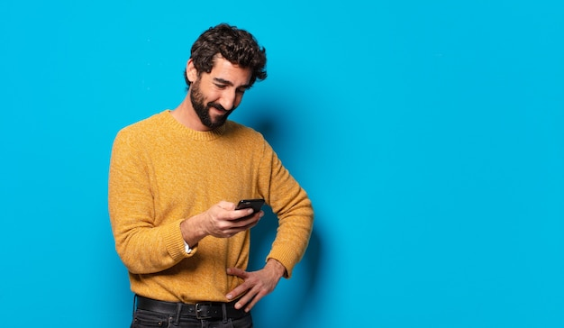 Giovane uomo barbuto pazzo che mostra il suo schermo di cella vuota