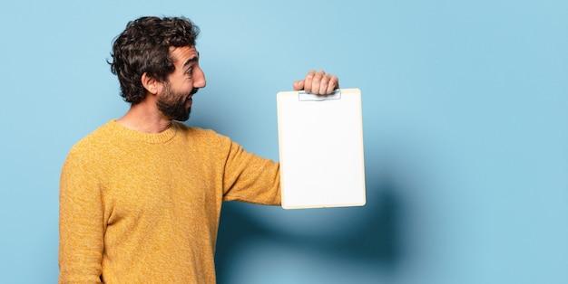 Giovane uomo barbuto pazzo che mostra un foglio di carta con uno spazio di copia