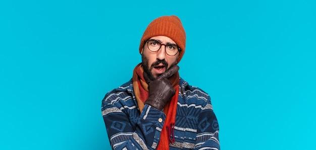 Giovane uomo barbuto pazzo. pensare o dubitare dell'espressione e indossare abiti invernali