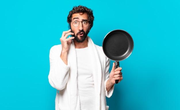 Giovane uomo barbuto pazzo che indossa un accappatoio che cucina con una padella
