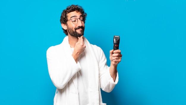 Giovane uomo barbuto pazzo che indossa accappatoio andando a radersi la barba