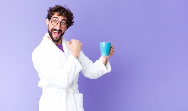 Giovane uomo barbuto pazzo che indossa accappatoio e avendo un caffè