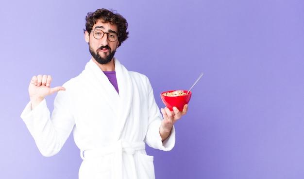 Giovane uomo barbuto pazzo che indossa accappatoio e che tiene una ciotola per la colazione