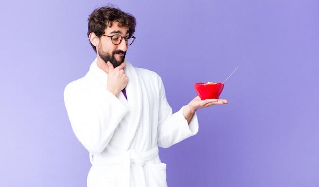 Accappatoio d'uso del giovane uomo barbuto pazzo e tenere una ciotola della prima colazione