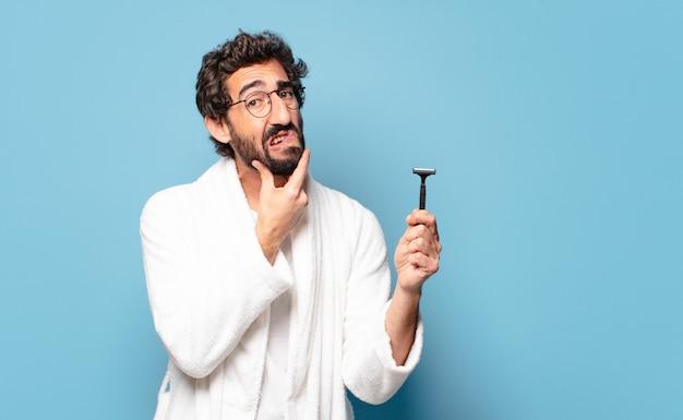 Giovane uomo barbuto pazzo che indossa accappatoio. tavola da barba