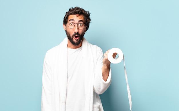 Giovane uomo barbuto pazzo che indossa accappatoio e carta igienica