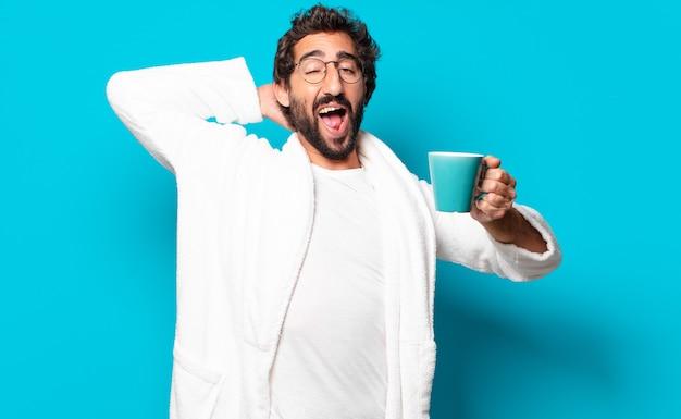 Giovane uomo barbuto pazzo indossando accappatoio con una tazza di caffè