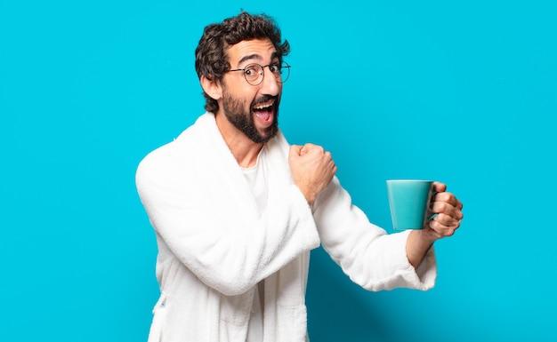 Giovane uomo barbuto pazzo che indossa accappatoio con una tazza di caffè