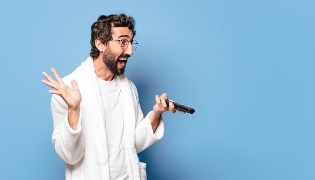 Giovane uomo barbuto pazzo che indossa un accappatoio con un telecomando