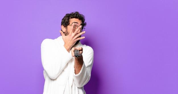 Giovane uomo barbuto pazzo che indossa accappatoio con un telecomando della televisione