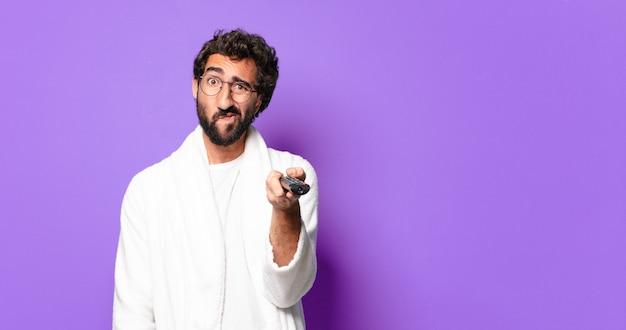 Giovane uomo barbuto pazzo indossando accappatoio con un telecomando della televisione