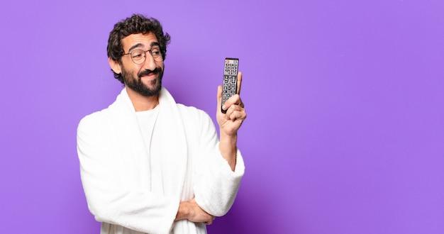 Giovane uomo barbuto pazzo che indossa un accappatoio con un telecomando della televisione