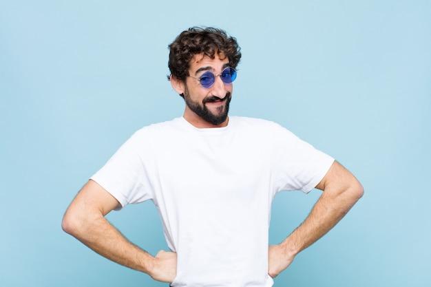 Giovane uomo barbuto pazzo indossando occhiali da sole