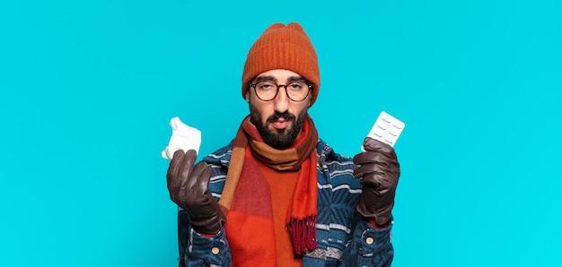 Giovane uomo barbuto pazzo e indossa abiti invernali. concetto di malattia
