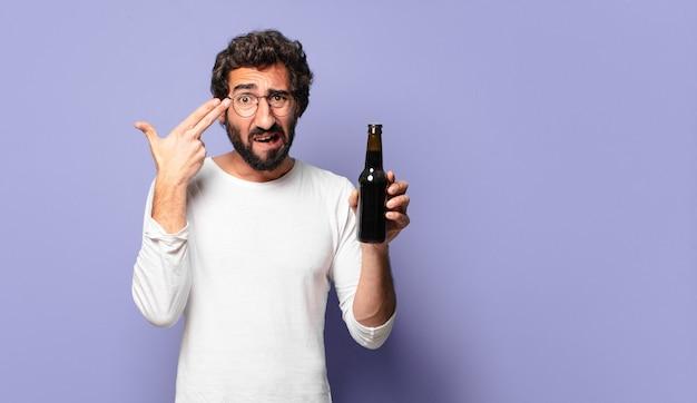 Giovane uomo barbuto pazzo con una birra