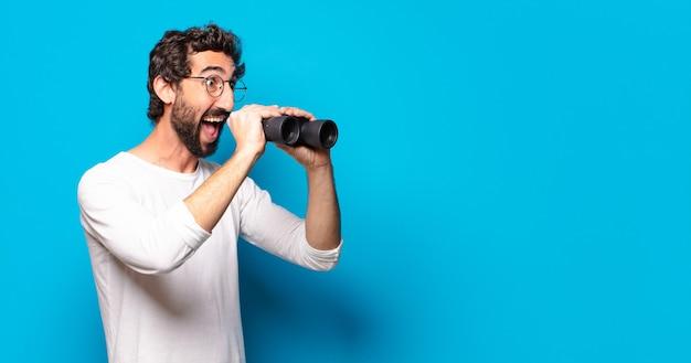 Giovane uomo barbuto pazzo con il binocolo